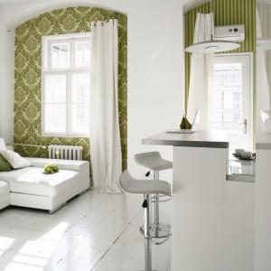 Niewielki, biały salon subtelnie ożywiono zieloną tapetą, naklejoną we wnękach okiennych. Projekt: Liliana Masewicz-Kowalska. Fot. Bartosz Jarosz.