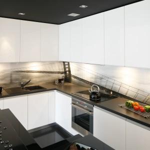 Gładkie, białe fronty szafek kuchennych elegancko kontrastują z czarnym blatem. Intrygującym rozwiązaniem jest czarny sufit, wieńczący górne, wysokie, białe szafki. Projekt: Joanna Ochota. Fot. Bartosz Jarosz.