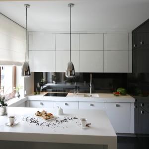 Częściowo otwarta kuchnia z półwyspem, w której czarna wysoka zabudowa na wysoki połysk pokrywa całą ścianę, a typową zabudowę jednorzędową tworzą białe meble, przedzielone pasem czarnej ściany. Projekt: Łukasz Sałek. Fot. Bartosz Jarosz.