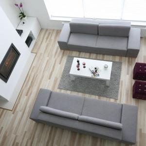W otwartej na dwie kondygnacje strefie dziennej zestaw wypoczynkowy tworzą dwie ulokowane równolegle względem siebie kanapy. Projekt: Artur i Karolina Urban. Fot. Bartosz Jarosz.