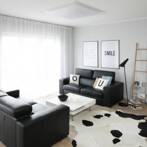 W urządzonym w minimalistycznym stylu salonie dwie dwuosobowe kanapy organizują przestrzeń dzienną. Rozlokowane równolegle względem siebie zamykają salon w wyraźne ramy. Projekt: Beata Kruszyńska. Fot. Bartosz Jarosz.
