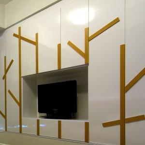 Fronty zabudowy meblowej udekorowano pasami dębowego drewna. Pełnią one rolę dekoracyjną i praktyczną, służąc za oryginalne uchwyty. Projekt: KNQ Associates. Fot. KNQ Associates.