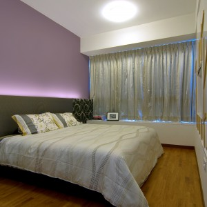 Ścianę za łóżkiem pomalowano na pastelowy kolor fiołkowego różu. Przyjemny kolor buduje przytulną atmosferę w sypialni. Wtóruje mu tekstylny zagłówek i eleganckie tekstylia. Projekt: KNQ Associates. Fot. KNQ Associates.