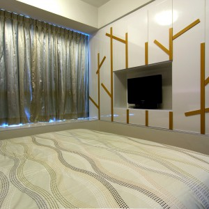 Jedną ze ścian w sypialni w całości zabudowano, pozostawiając jedynie wnękę na TV. Wykończone na połysk fronty korespondują z lekko połyskującymi tkaninami. Projekt: KNQ Associates. Fot. KNQ Associates.