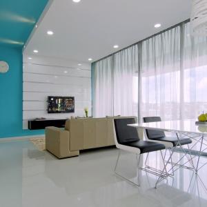 Salon i jadalnia tworzą wspólną przestrzeń, połączoną w spójną całość za pomocą jednorodnej podłogi i dużych przeszkleń, pokrywających całą ścianę. Projekt: KNQ Associates. Fot. KNQ Associates.