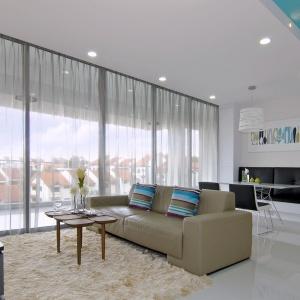 Biały podwieszany sufit łączy wizualnie dwie odrębne funkcje strefy dziennej. Przechodzący w panel za TV na jednej ścianie, scala się kolorystycznie z zabudową w jadalni, w której uformowano wygodne siedzisko na ścianie przeciwległej. Projekt: KNQ Associates. Fot. KNQ Associates.