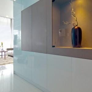 W strefie wnętrza białą zabudowę urozmaica szarobeżowy akcent z wnęką, w której ustawiono dekoracyjną wazę, efektownie oświetloną zamontowanym w zabudowie oświetleniem. Projekt: KNQ Associates. Fot. KNQ Associates.
