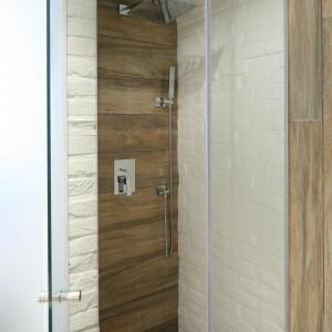 Kabinę prysznicową tworzą wąska ścianka boczna oraz otwierane wahadłowo drzwi. Zamiast brodzika – odpływ liniowy wposadzce. Fot. Bartosz Jarosz.
