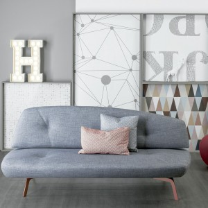 Niewielka, szara sofa Bandy o anatomicznym kształcie. Zmysłowy charakter mebla podkreślają cienki nóżki w beżowym kolorze. Fot. Bonaldo.