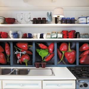 Kolorowe naklejki to tani i szybki sposób na urozmaicenie aranżacji kuchni. Naklejka z kolażem zdjęć czerwonych papryczek pięknie kontrastuje z białym blatem. Fot. Pixers.