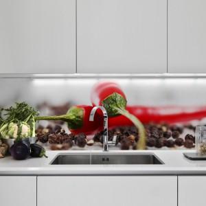 Białą kuchnię w minimalistycznym stylu ożywiają czerwone papryczki chilli w formie pięknej fototapety. Fot. Minka.