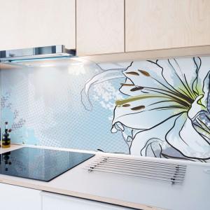 Ścianę nad blatem pokrywa piękna fototapeta w odcieniach wpadającego w biel błękitu. Zdobi ją grafika z pięknym rysunkiem rozwijającego się kwiatu. Fot. Minka.