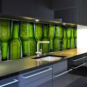 Czarna kuchnia w wysokim połysku została ożywiona fototapetą z motywem soczyście zielonych... butelek. Ustawione jedna przy drugiej w ciekawy wzór na fotografii zdobiącej ścianę, intrygują i przyciągają wzrok. Fot. Minka.