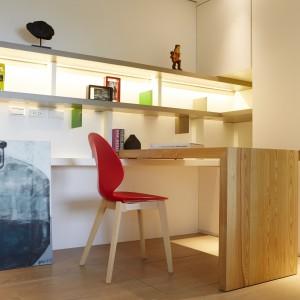Niewielki gabinet zaprojektowano z troską o funkcjonalność rozwiązań i maksymalne wykorzystanie przestrzeni. Wysoka zabudowa, połączona została z praktycznymi półkami, które z kolei posłużyły za podstawę dla posadowienia biurka. Projekt: J.C. Architecture. Fot. Hedy Chang.