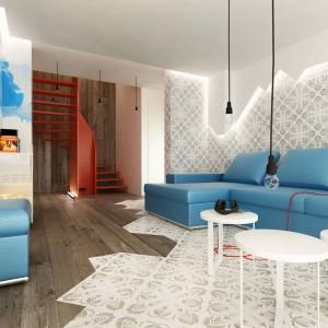 Przestrzeń typowo wypoczynkową wyodrębniono przy pomocy oryginalnej okładziny na ścianie za kanapą, która rozciąga się także na podłodze. Fot. PressEnter Design.