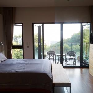 Przestrzeń nad łóżkiem w sypialni zabudowano, pozostawiając wnękę z miejscem na montaż lampek nocnych. Podnóżek oraz regał, pełniący funkcję elementu działowego, wykonano w drewnie. Projekt: J.C. Architecture. Fot. Hedy Chang.