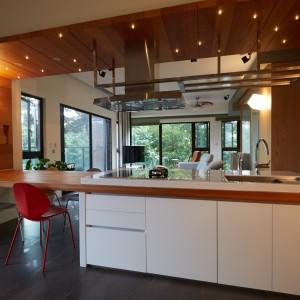 Dużą, praktyczną wyspę połączono drewnianym blatem z zabudową ścienną. Ta z kolei przechodzi płynnie w pas drewna na suficie, w którym zainstalowano oświetlenie. Projekt: J.C. Architecture. Fot. Hedy Chang.