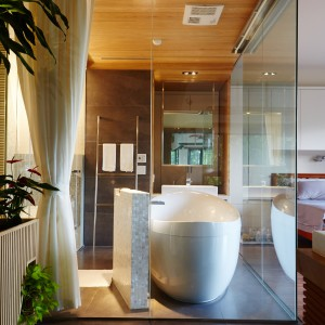 Zamiast ścianek działowych, łazienkę okalają duże, przeźroczyste przeszklenia. Projekt: J.C. Architecture. Fot. Hedy Chang.