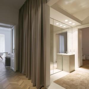 Umieszczona pomiędzy holem a sypialnią małżeńską łazienka, została częściowo otwarta. Od korytarza oddziela ją tekstylna kurtyna. Projekt: destilat Design Studio. Fot. Monika Nguyen.