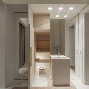 Za piękną, stojącą umywalką zaplanowano całkowicie przeszkloną powierzchnię, która po otwarciu drzwiczek odkrywa... domową saunę! Projekt: destilat Design Studio. Fot. Monika Nguyen.