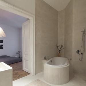 Łazienka przybrała formę ekskluzywnego salonu kąpielowego, połączonego z sypialnią małżeńską podwójnymi, typowymi dla starego budownictwa drzwiami. We wnękę wpasowano wannę a tuż obok wygospodarowano miejsce na strefę prysznica. Projekt: destilat Design Studio. Fot. Monika Nguyen.