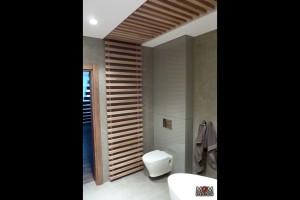 W łazience również zamontowano nowoczesne rozwiązania. Dekoracyjnie wnętrze przełamano drewnem. Fot. MGM Design