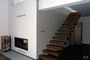 Salon ociepla panoramiczny, prosty kominek, a tuż za nim, na górę prowadzą schody dające efekt zawieszonych w powietrzu. Fot. MGM Design