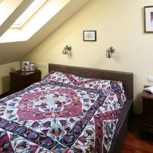 Sypialnię na poddaszu urządzono bazując na ciepłej palecie jasnych, beżowych odcieni i brązów. Najbardziej charakterystycznym elementem jest kolorowe narzuta. Projekt: Magdalena Misaczek. Fot. Bartosz Jarosz.