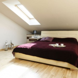 Przestronna sypialnia na poddaszu została urządzona bardzo funkcjonalnie. Poza wygodnym łóżkiem i szafkami nocnymi znajdziemy tutaj toaletkę oraz sporo miejsca na przechowywanie. Projekt: Jolanta Kwilman. Fot. Bartosz Jarosz.