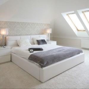 Sypialnia urządzona jest w stylu glamour. Dekoracyjne formy oświetlenia i bogato zdobiona tapeta w połączeniu z prostą, białą ramą łóżka tworzą spójne, estetyczne wnętrze. Projekt: Karolina i Artur Urban. Fot. Bartosz Jarosz.