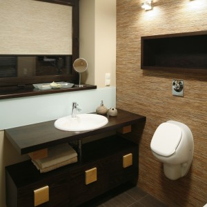 Drewniane elementy podkreślają ciepły charakter łazienki przy sypialni, zwłaszcza że idealnie dobrano do nich płytki, przypominające fakturą i kolorem usłojone drewno. Projekt: Kasia i Michał Dudko. Fot. Bartosz Jarosz.
