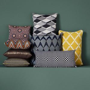 Designerskie geometryczne wzory poduszek świetnie sprawdzą się w niemal każdym wnętrzu. Wzory zachwycają przestrzennością i złudzeniami optycznymi. Do nabycia w BoConcept. Cena poduszki Formula (czarno-biało-szara na górze) - 199 zł. Fot. BoConcept.