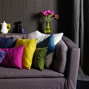 Piękne poduszki w soczystych kolorach dobrane jako ożywczy element ciemnego salonu. Wykonane z materiałów dostępnych w firmie Elitis. Fot. Elitis.