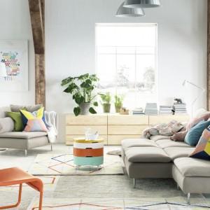 Poduszki w geometryczne wzory kolorystycznie pasują do stolika kawowego i grafiki na ścianie. Dobieranie poszewek do innych elementów wystroju to świetny pomysł na ożywienie przestrzeni. Fot. IKEA.