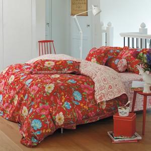 Czerwoną pościel projektu PiP Studio Bettwäsche, zdobią beżowe, błękitne i różowe kwiatki. Dzięki niej łóżko wygląda jak oryginalna, kolorowa łąka. Fot. Art Chateau.