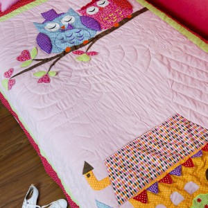 Aplikacja z kolorowej tkaniny zdobi poduszkę oraz kołdrę, w podobnych odcieniach różu. Fot. Milvai.