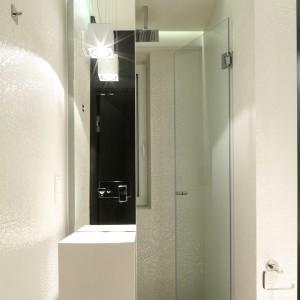Nietypowy pomysł na strefę prysznica: lustro nad umywalką oraz sama umywalka podłogowa pełni rolę ścianki prysznicowej, która łączy się ze szklanymi drzwiami. Takie rozwiązanie jest oryginalne i praktyczne - w bardzo małej łazience można wygodnie korzystać z prysznica. Projekt: Dominik Respondek. Fot. Bartosz Jarosz.
