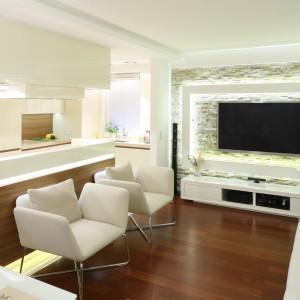 W zintegrowanej strefie dziennej kuchnia płynnie łączy się z salonem. Wszechobecna biel powiększa optycznie jej przestrzeń, a dekor drewna ją wizualnie ociepla. Projekt Małgorzata Mazur. Fot. Bartosz Jarosz.