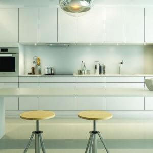 Biała zabudowa kuchenna z wnęką, w którą wpasowano powierzchnię roboczą. Minimalistyczne białe fronty bez uchwytów, tworzą jednorodną, satynową powierzchnię. Fot. Sigdal.