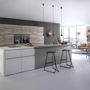 Duża, dwukolorowa wyspa kuchenna z frontami wykończonymi w matowej bieli i szarości pięknie komponuje się z wysoką zabudową z drewnianym dekorem. Fot. Leicht, kuchnia Synthia C|Ceres C.