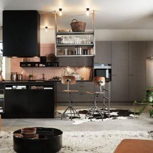 Piękna kuchnia, otwarta na salon, w której matowa zabudowa stanowi delikatne tło dla dodatków dekoracyjnych. Bardziej wyeksponowana wyspa kuchenna została wykończona w czerni - również w macie. Fot. Ballingslov.
