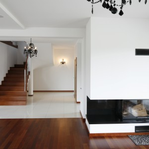 Eleganckie, drewniane schody, wykonane z takiego samego materiału jak podłoga, są ciekawym urozmaiceniem nowoczesnego, białego salonu. Fot. Piotr Stanisz. Fot. Bartosz Jarosz.