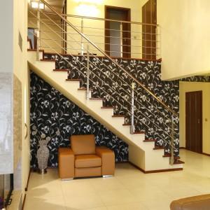 Aby podkreślić ważną rolę, również dekoracyjną schodów, ścianę przy nich ozdobiono elegancką tapetą. Ustawiony pod nimi fotel jest niezastąpiony np. w trakcie zmiany obuwia. Projekt: Piotr Stanisz. Fot. Bartosz Jarosz.