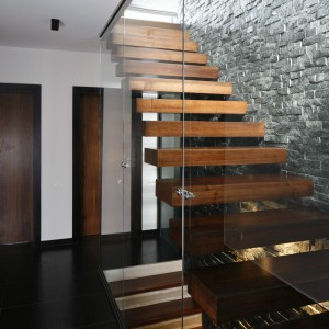 Jako balustradę wykorzystano taflę szkła, która nie odwraca uwagi od dekoracyjnego łupka wyłożonego na ścianie. Projekt: Wielecki&Hoffman. Fot. Bartosz Jarosz.