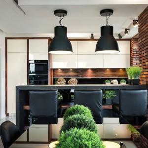 Cegła na ścianie i industrialne oświetlenie nad półwyspem kuchennym, pełniącym również funkcję domowego baru, sprawiają, że kuchnia nabiera loftowego charakteru. Projekt: Małgorzata Błaszczak. Fot. Pracownia Mebli Vigo/Artur Krupa.
