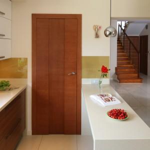 W prostej beżowo-białej kuchni cegła na ścianie stanowi istotny element dekoracyjny, nadający wnętrzu charakter. Utrzymana w kolorach jasnego brązu wtapia się w otaczające ją kolory. Projekt: Magdalena Bonin-Jarkiewicz. Fot. Bartosz Jarosz.