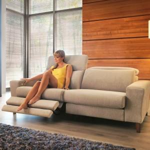 Dwuosobowa sofa z funkcją relaks marki Unimebel. Umiejscowiony przy podłokietniku mechanizm pozwala w wygodny sposób rozłożyć podnóżkową część mebla. Beżowe obicie dodatkowo pomaga stworzyć we wnętrzu przytulny klimat. Fot. Unimebel.