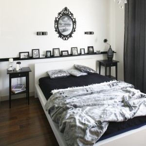 Ciemna, drewniana podłoga, czerń i biel – to przepis na piękne, eleganckie wnętrze. Stylizowane lustro nad łóżkiem wprowadza do sypialni lekko glamourowy klimat. Projekt: Małgorzata Mazur. Fot. Bartosz Jarosz.