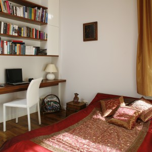 Ciemna, drewniana podłoga i szafki w tym samym kolorze stanowią znakomity kontrast z zastosowaną w sypialnia kolorystyką. Pasują zarówno do bieli, jaki i do bardziej barwnej narzuty na łóżku. Projekt: Iwo Kęsy. Fot. Bartosz Jarosz.