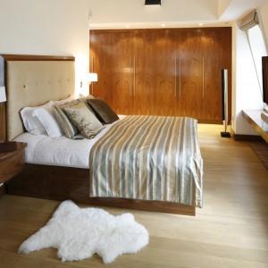 W tej sypialnia drewno nadaje charakter całej aranżacji sypialni. Sprawia, że jest ona ciepła i bardzo przytulna – doskonała na sen i popołudniowy odpoczynek. Mimo, iż zastosowane drewno ma różną kolorystykę – inną na podłodze, a inną na ramie łóżka czy szafkach – wspólnie tworzy spójną i bardzo estetyczną całość. Projekt: Studio KPP. Fot. Bartosz Jarosz.